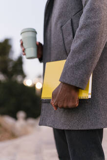 Young man wearing coat holding book and disposable cup standing outdoors - EGAF01523