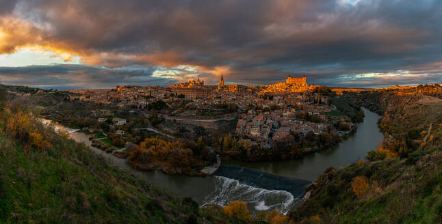 View across river of old city Toledo in Spain with medieval castles and fortresses at sunset time with cloudy sky and reflection in river water - ADSF20273