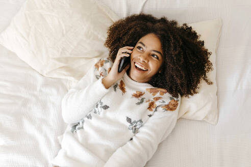 Excited woman talking on mobile phone while lying on bed at home - TCEF01472