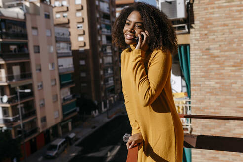 Curly hair woman talking on mobile phone while standing at balcony - TCEF01487