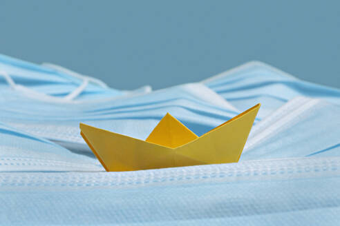 Yellow origami boat on disposable blue face masks - FSIF05604