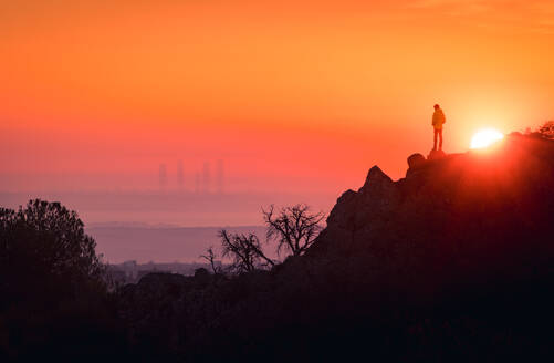 Remote view of unrecognizable tourist standing on rock and enjoying view of Madrid at sundown - ADSF20347