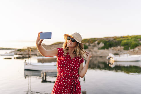 Smiling woman wearing hat taking selfie through mobile phone while standing against sky - DGOF01844