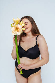 Smiling female model wearing black bikini smelling flowers against white background - OIPF00101