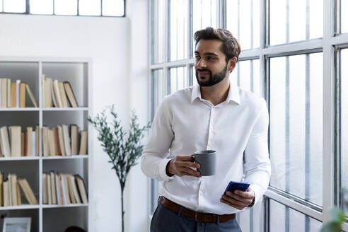 Smiling businessman with mobile phone holding coffee cup while looking away in office - GIOF10838