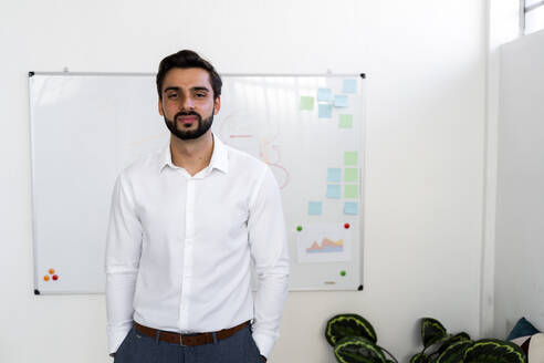 Smiling young businessman with hands in pockets standing against whiteboard at work place - GIOF10883