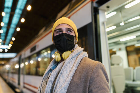 Man wearing face mask looking away while standing against train at station - EGAF01566