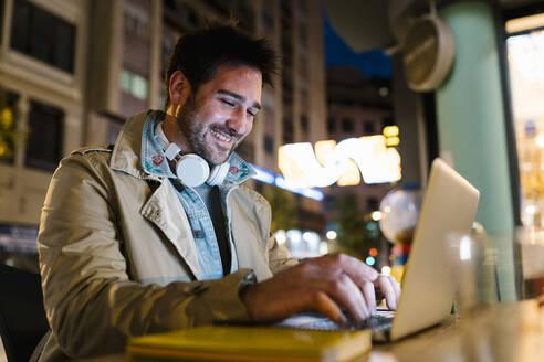 Smiling man using laptop while sitting at sidewalk cafe - EGAF01572