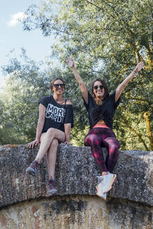 Cheerful female friends sitting on old wall against trees - JRVF00184