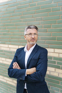 Confident mature businessman with arms crossed standing against wall - PESF02552