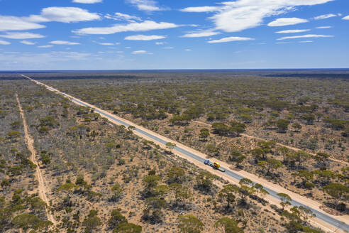Aerial view of Eyre Highway stretching across Nullarbor National Park with clear line of horizon in background - FOF12010