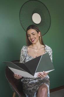 Smiling businesswoman reading file while sitting on chair against green wall - DSIF00274