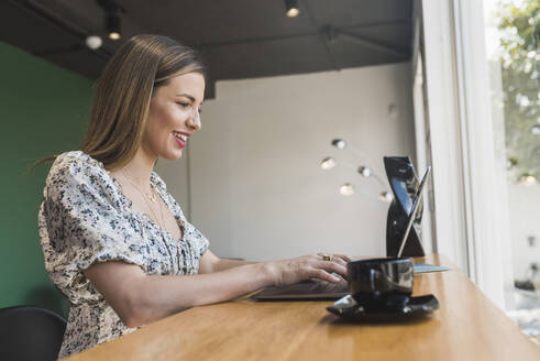 Smiling businesswoman working over laptop on table in cafe - DSIF00277