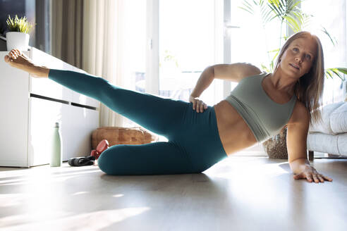 Young woman lying on side while exercising at home - JSRF01265