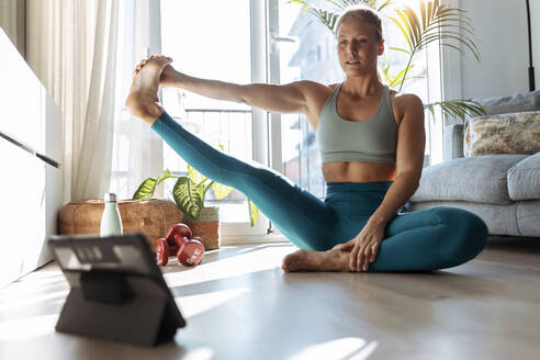 Young woman stretching leg while using digital tablet during workout at home - JSRF01268