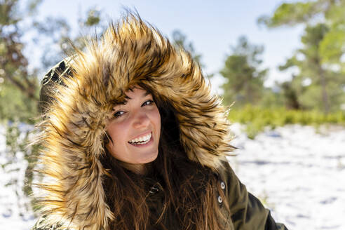 Smiling young woman wearing fur hooded winter coat staring while standing in forest - DLTSF01558
