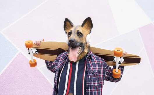 Young woman wearing dog mask carrying skateboard on shoulders while standing against wall - JCCMF00939