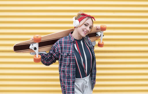 Young woman smiling while carrying skateboard on shoulder against yellow wall - JCCMF00951