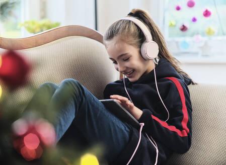 Mädchen(9) mit iPad und Kopfhörer auf Sofa mit Weihnachtsdeko hört Musik / Hörspiel oder zockt - DIKF00546