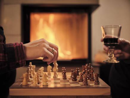 Paar spielt Schach vor Kaminfeuer. Winterabend. Weinglas. - DIKF00552