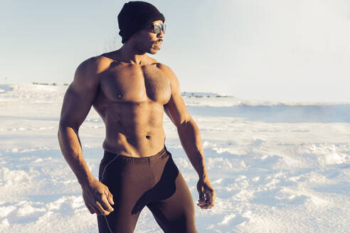 Muscular build sportsman looking away while standing in snow - JCCMF01017
