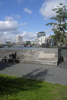 Germany, Hamburg, Riverbank benches in HafenCity with bridge and modern apartments in background - GISF00743