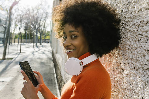 Smiling Afro woman with smart phone and headphones at public park - XLGF01054