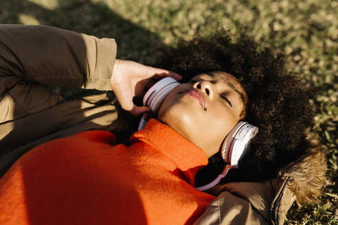 Afro woman with eyes closed listening music on grass during sunny day - XLGF01075