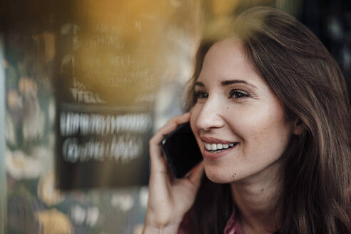 Female professional smiling while talking on smart phone at cafe - JOSEF03165