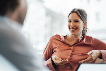 Businesswoman laughing while discussing with male colleague in cafe - JOSEF03198