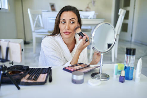 Female influencer applying make-up while vlogging on smart phone at home - KIJF03521