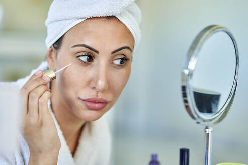 Beautiful woman applying beauty serum while looking in mirror at home - KIJF03530