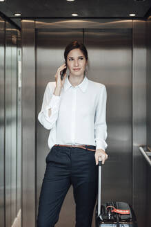 Businesswoman with suitcase taking on smart phone while standing in elevator - JOSEF03261