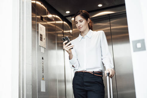 Businesswoman text messaging on mobile phone while standing in elevator - JOSEF03333