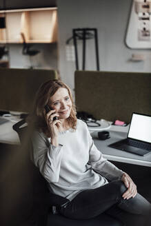 Smiling businesswoman talking over smart phone while working at desk in office - JOSEF03351