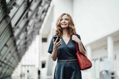 Senior businesswoman with smart phone in corridor at office - JOSEF03384