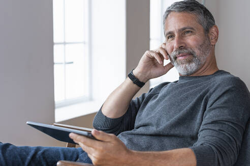 Thoughtful businessman looking away while sitting with digital tablet at home - SBOF02587