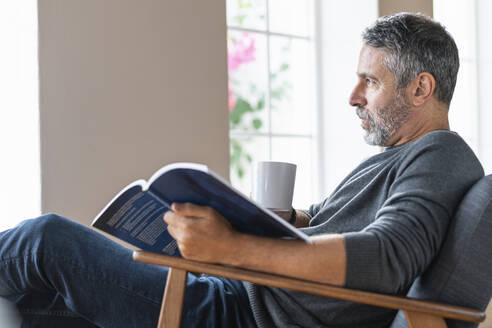 Thoughtful businessman looking away while sitting with book and coffee cup on armchair at home - SBOF02590