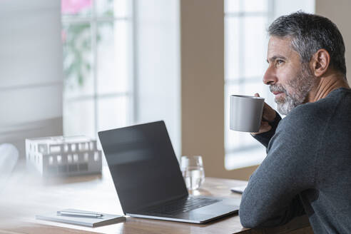 Mature businessman drinking coffee while sitting at home office - SBOF02596