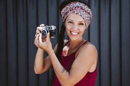 Smiling woman adjusting camera lens while standing against wall - EBBF02364