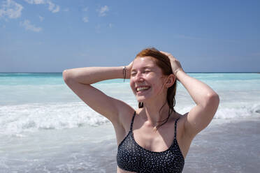 Cheerful young woman standing with hand in hair at beach during sunny day - LBF03325