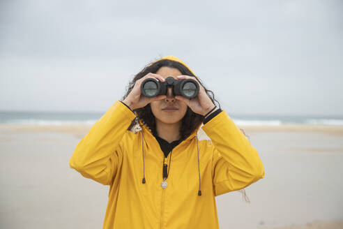 Woman using binoculars while standing at beach - KBF00703