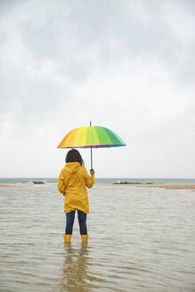Young woman holding umbrella while standing in water at beach - KBF00706