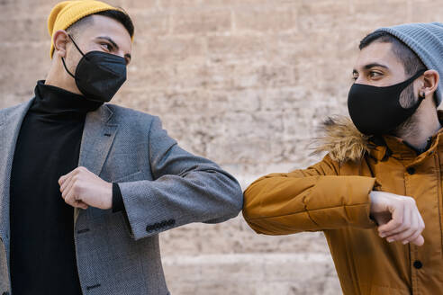 Male friends wearing protective face mask and knit hat giving elbow bump while standing against wall - EGAF01624