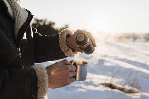Man pouring hot coffee in cup through thermos on sunny day - EBBF02387