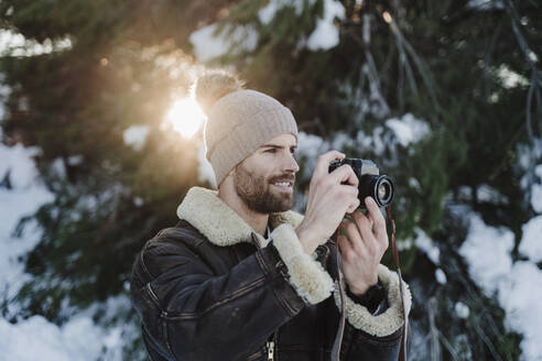 Handsome man photographing through camera against trees during winter - EBBF02390