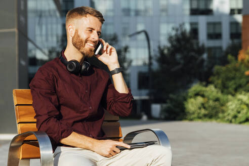 Businessman talking on mobile phone while sitting on bench during sunny day - BOYF01655