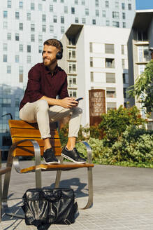 Smiling businessman wearing headphones looking away while using mobile phone sitting on bench in city - BOYF01658