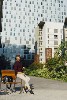 Male entrepreneur with mobile phone looking away while sitting in city - BOYF01661
