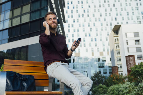Mid adult businessman listening through headphones while sitting on bench in city - BOYF01664